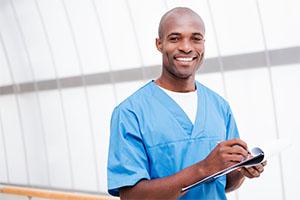 male nurse in blue scrubs smiling
