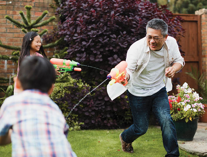 dad and kids playing with water guns