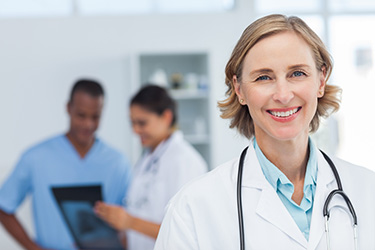 Female physician in white coat smiling