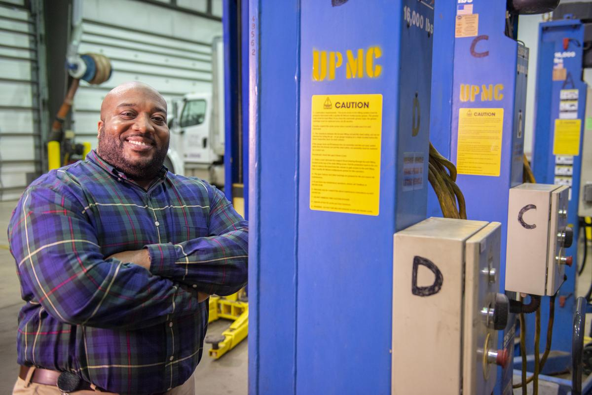 male UPMC employee standing next to a piece of equiptment, smiling