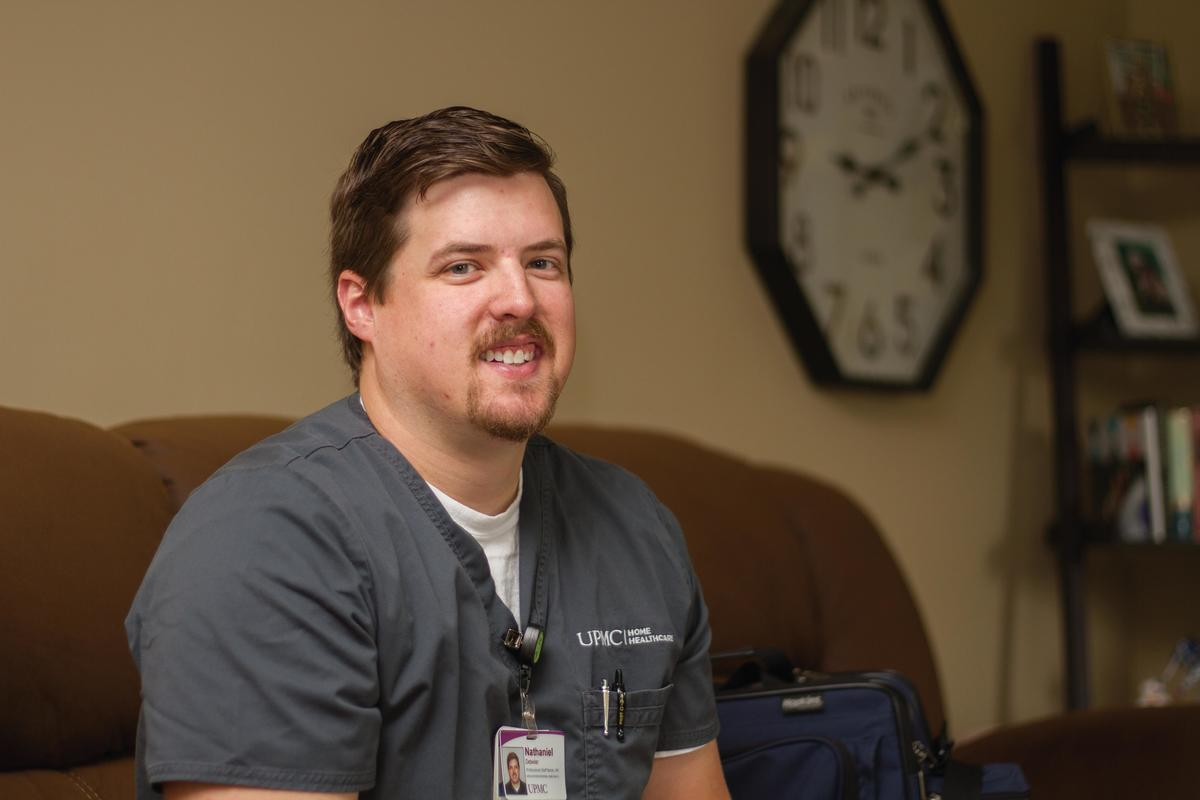male UPMC Home Healthcare employee inside of a patients home, smiling