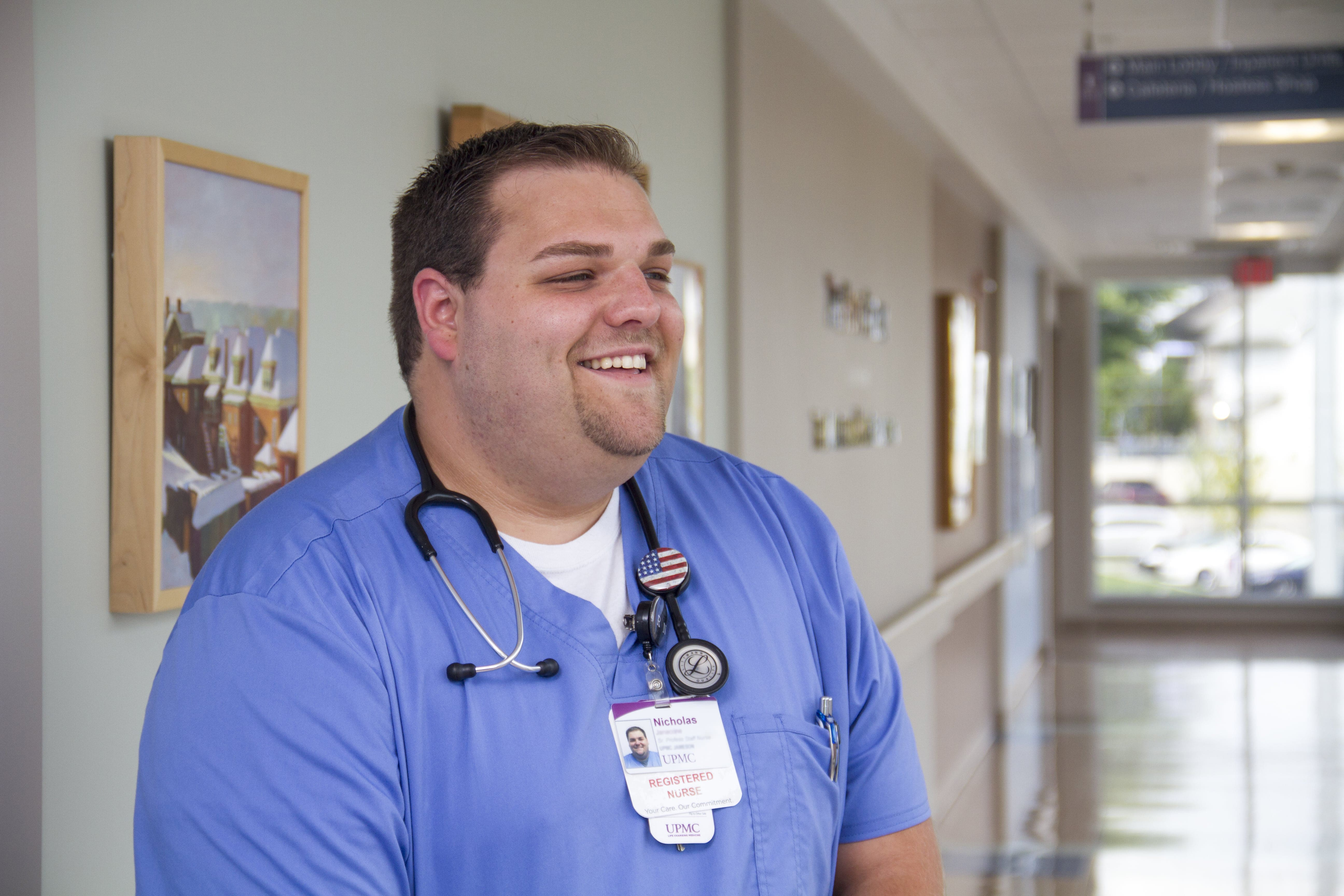 Graduate Nurse standing in the hallway of hospital, smiling