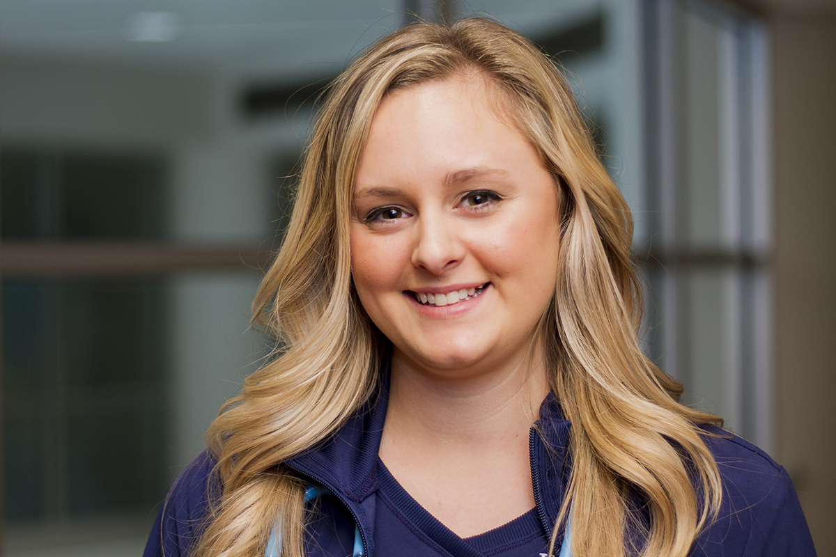 Head shot of female nurse wearing blue scrubs smiling