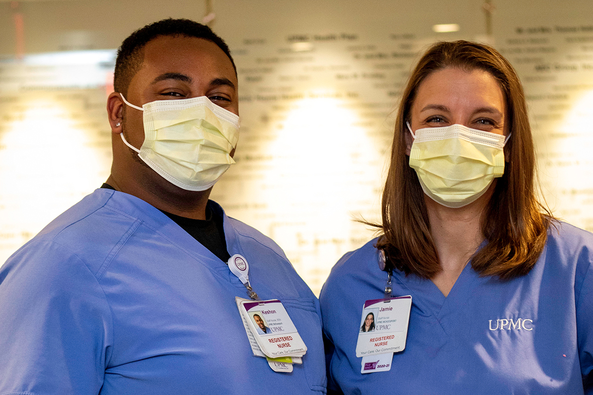 Two nurses in blue scrubs standing next to one another wearing masks